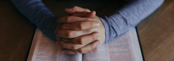 Foldede hender som hviler på bibelen